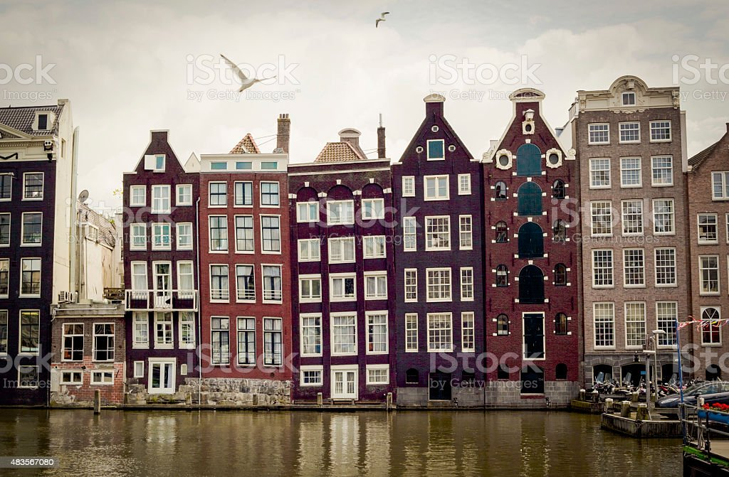 Row of typical houses along Amsterdam canal with seagulls stock photo