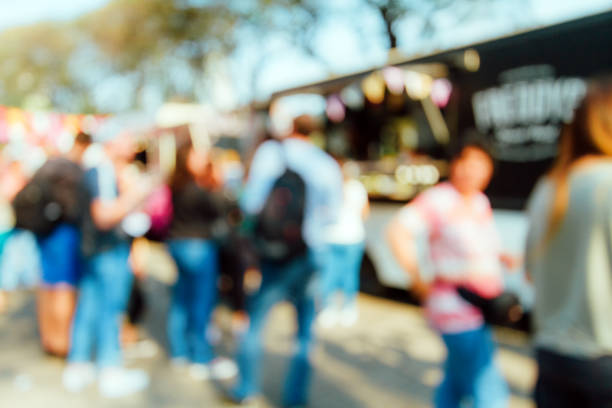Row of unfocused people lining up to buy in a Food Truck stock photo