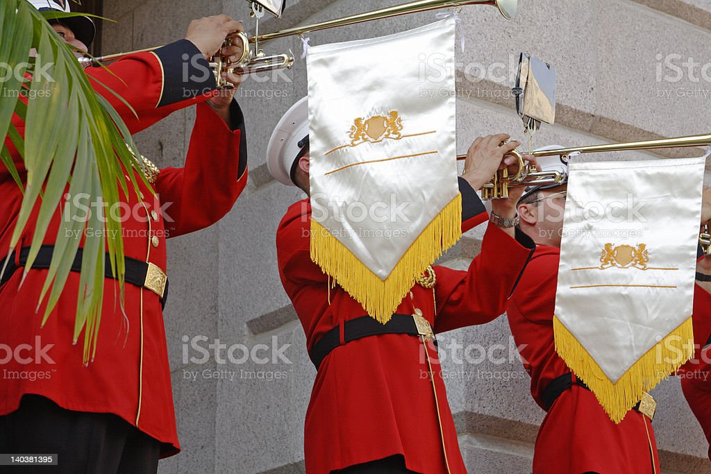 Row of uniformed men sounding their horns at official function royalty-free stock photo
