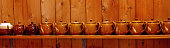 A row of little brown teapots all in a row on a shelf against a timber wall