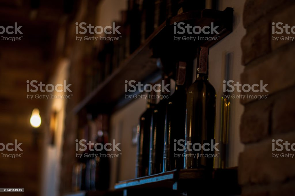 Row of vintage wine bottles in a wine cellar on wooden shelves