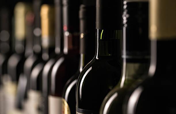 row of vintage wine bottles - şarap stok fotoğraflar ve resimler