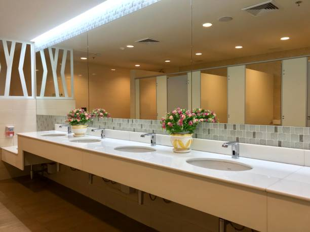 Row of wash sink with big mirror in public toilet stock photo