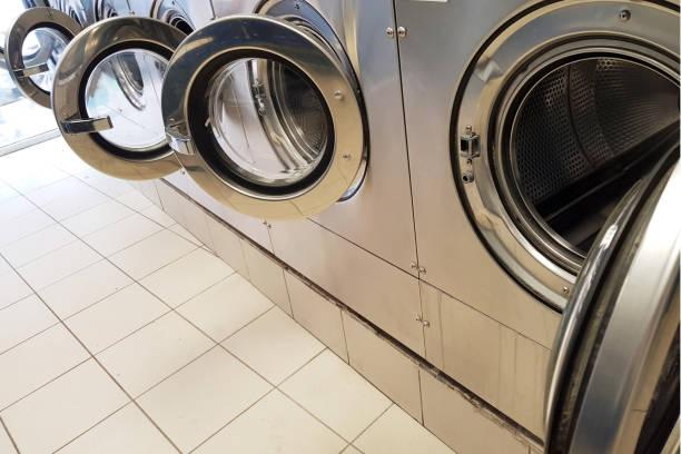 reihe von waschmaschinen in einer selbstbedienungs-automatik - leise waschmaschine stock-fotos und bilder
