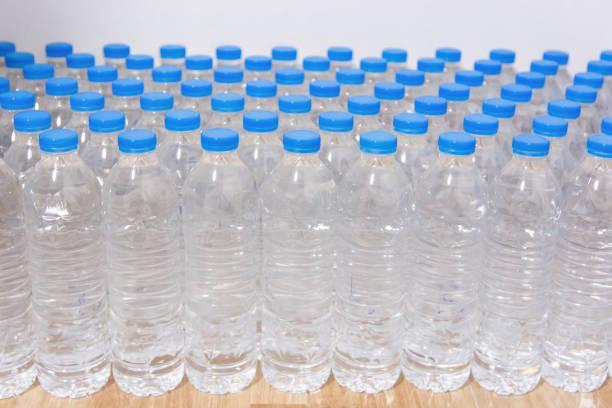 linha de garrafas de água. frascos com tampas azuis para água potável - sports water bottle - fotografias e filmes do acervo