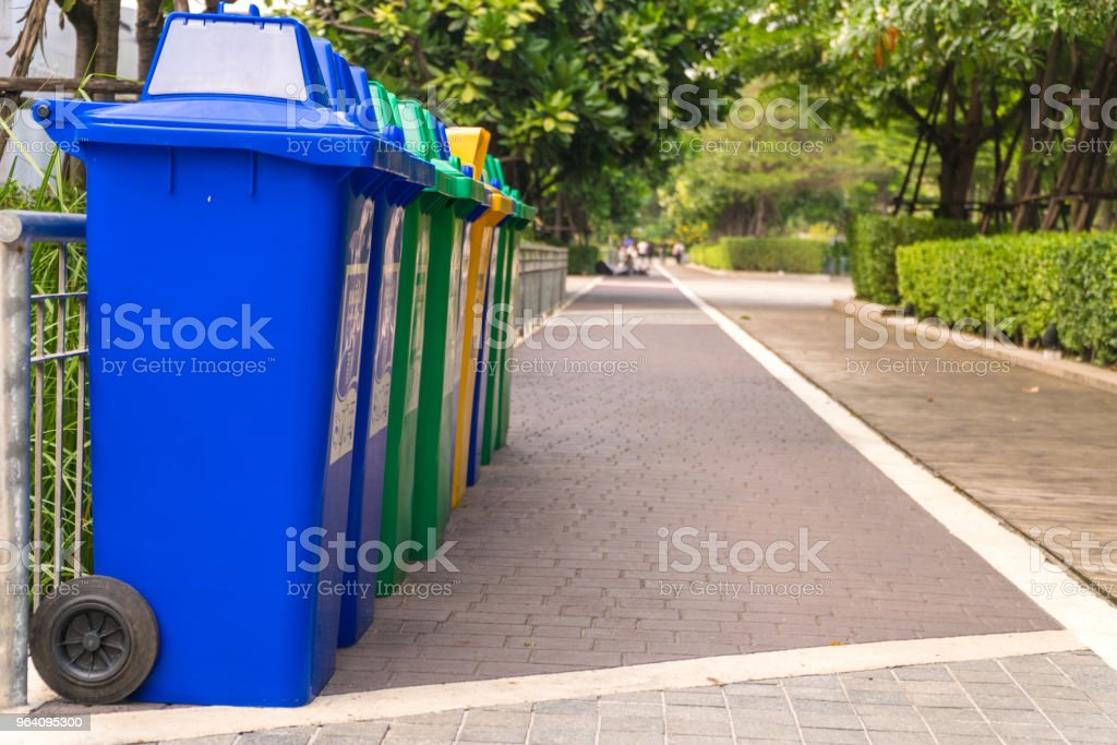 Row of Wheelie Bins. Many trash carts set in the park. There are blue, green and yellow tanks. Copy space. - Royalty-free Backgrounds Stock Photo