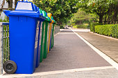 istock Row of Wheelie Bins. Many trash carts set in the park. There are blue, green and yellow tanks. Copy space. 964095300