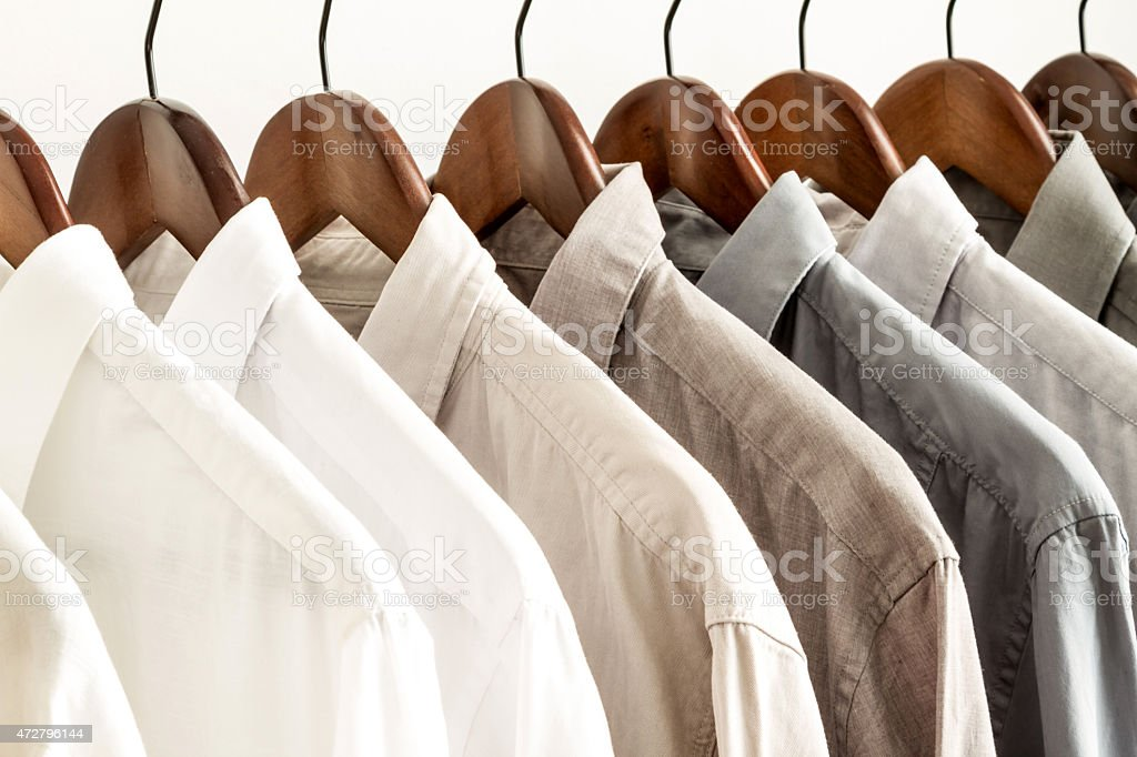 Row of white and beige shirts on wooden hangers  stock photo