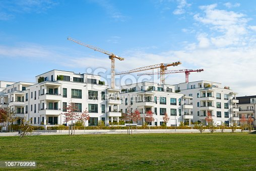 Brand new luxury townhouses and clear sky in Duesseldorf, Germany, three cranes of a construction area behind the buildings.