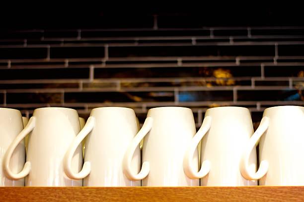 row of white cups/mugs neatly lined up on shelf - küchenorganisation stock-fotos und bilder