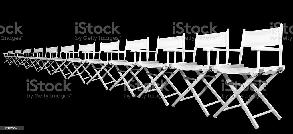 Row of white directors chairs on black background stock photo