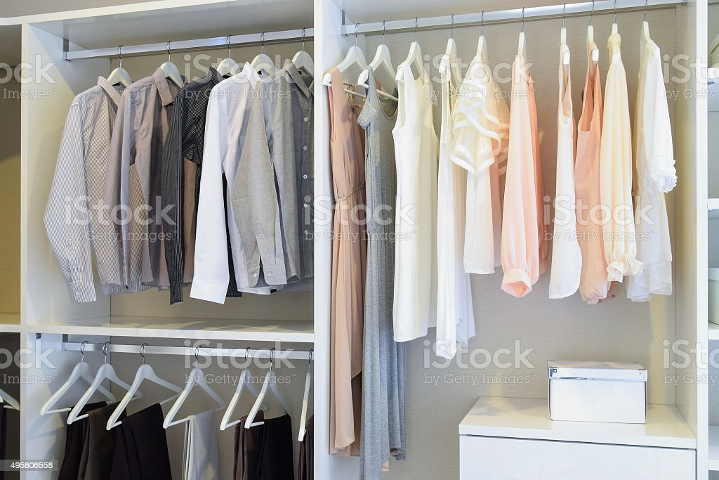 row of white dress and shirts hanging in white wardrobe stock photo