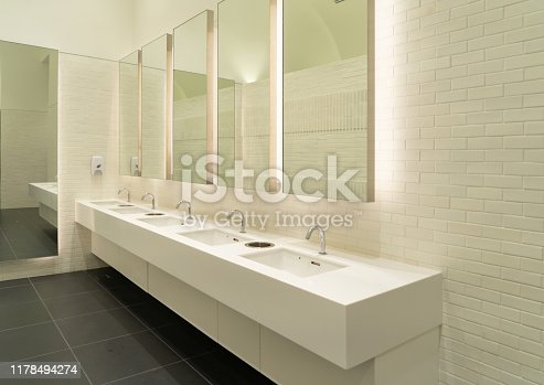 Row of white modern marble ceramic wash basin in public toilet, restroom in restaurant or hotel or shopping mall, interior decoration design