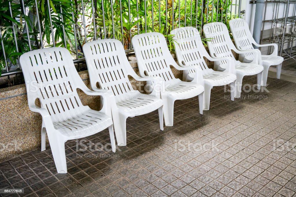 Row of white plastic outdoor chairs with backrest by swimming pool on brown mosaic tile floor against metal rails. stock photo