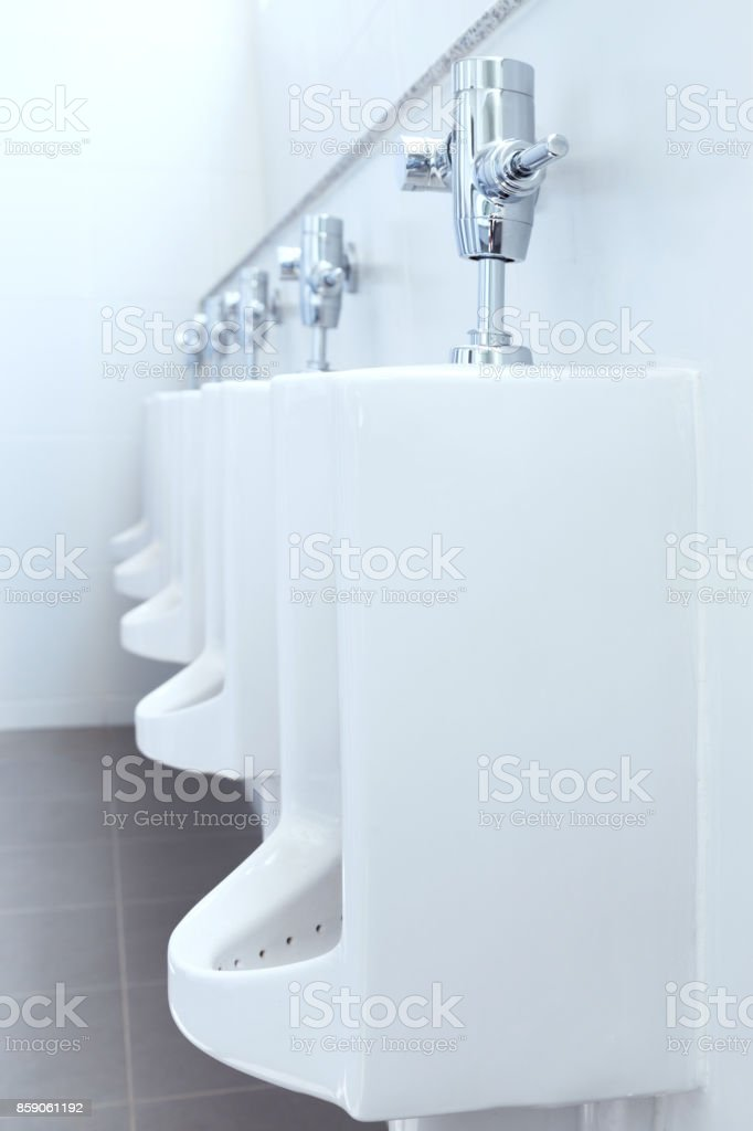 row of white urinals ceramic in public toilet or restroom. selective focus. stock photo