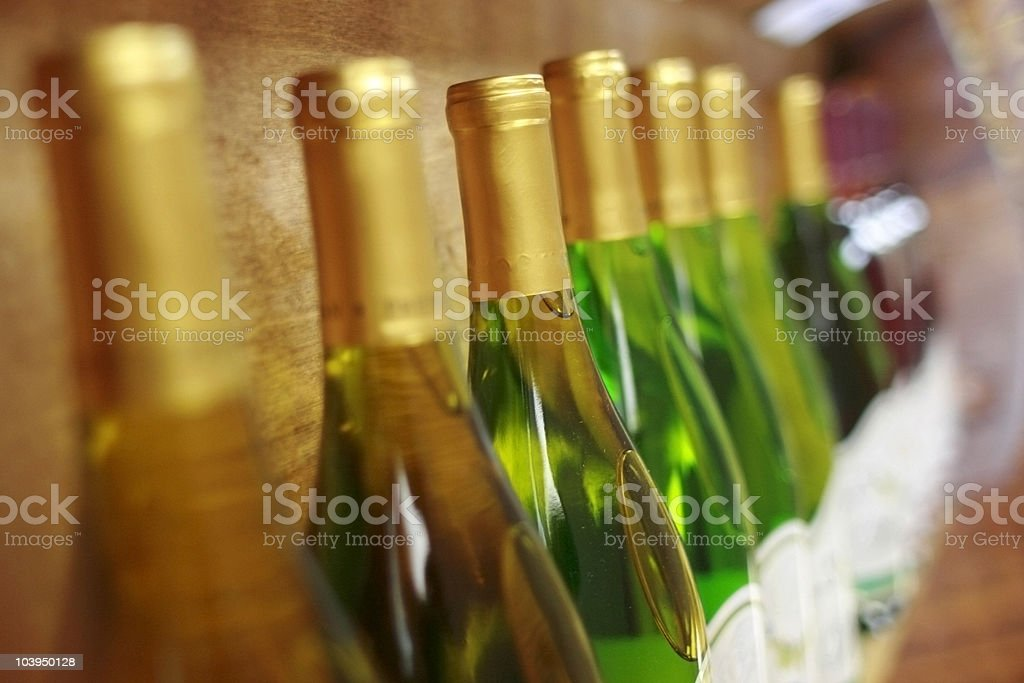 Row of White Wine Bottles in a Wooden Rack royalty-free stock photo