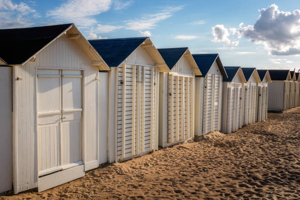 Row of white wooden beach huts or cabins alongside Riva Bella beach on early evening, Ouistreham, Normandy, France. stock photo