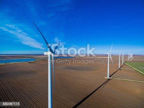 892160114 istock photo Row of wind turbines against blue sky 530487174