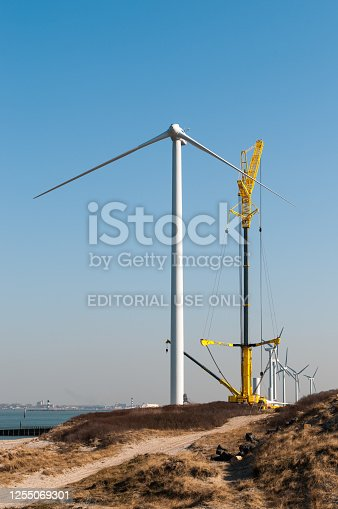 A modern windmill or turbine with 3 blades is being assembled on the Maasvlakte near Rotterdam. These turbines are powered by wind and convert the kinetic energy into so called green energy.