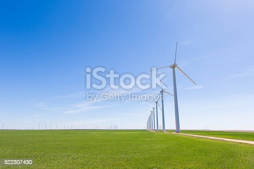 A row of windmills stand tall against a bright blue sky. They are surrounded by green grass. The windmills create renewable energy.