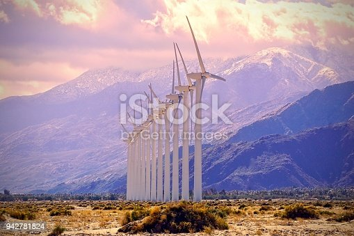 many wind turbines in the desert with mountain background and volatile weather