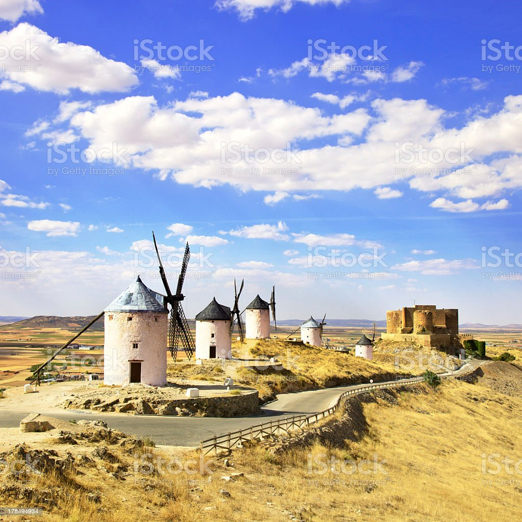 A row of windmills and a castle in Consuegra, Spain stock photo