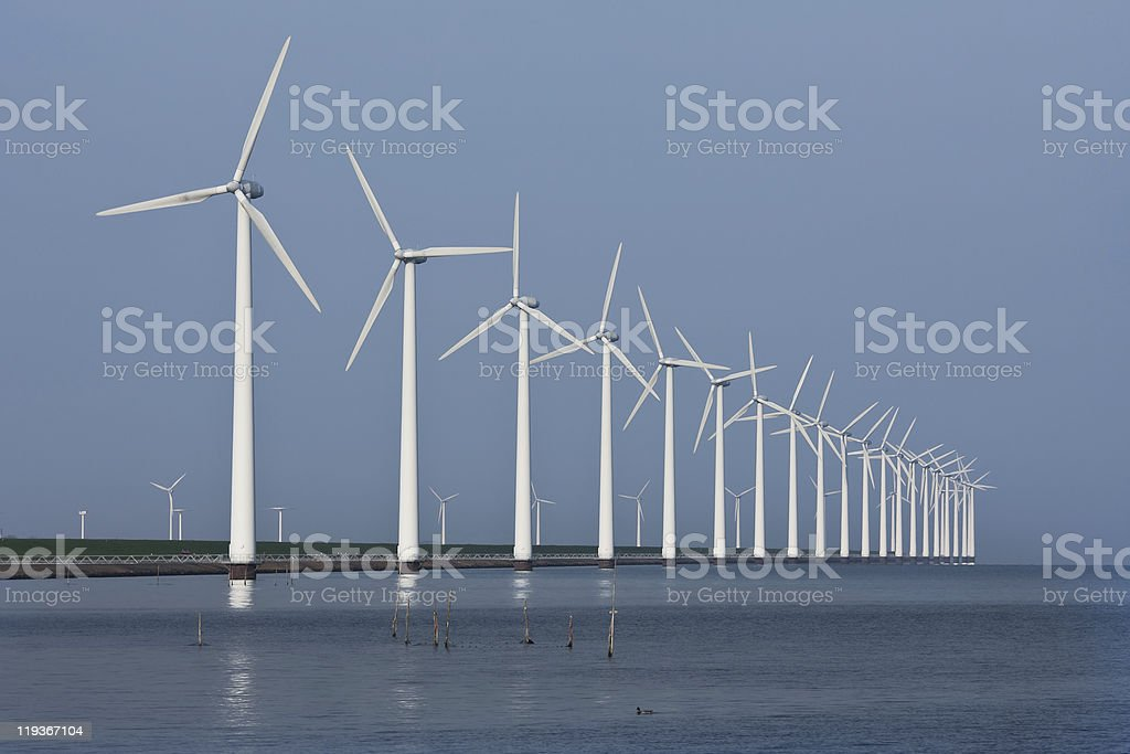 Row of windmills, mirrored in the Dutch sea royalty-free stock photo