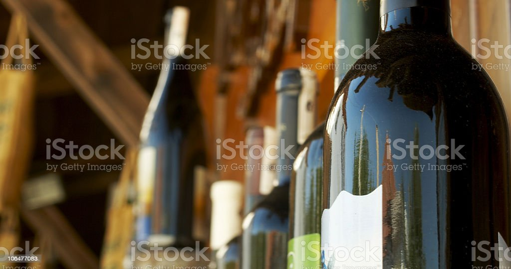 Row of wine bottles in wooden area stock photo