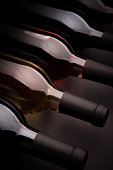 Abstract shot of various varieties of wine, bottled and in a row, against a black background.