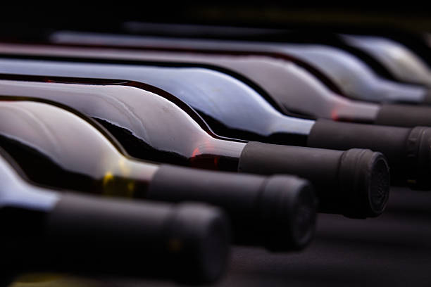 row of wine bottles - halbergman stock pictures, royalty-free photos & images