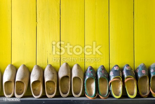 Row of pairs of used wooden shoes placed in line against a bright yellow wooden wall. Some wooden shoes are painted in traditional dutch pattern. Others are blank. The wooden shoes are part of the dutch culture in the Netherlands.