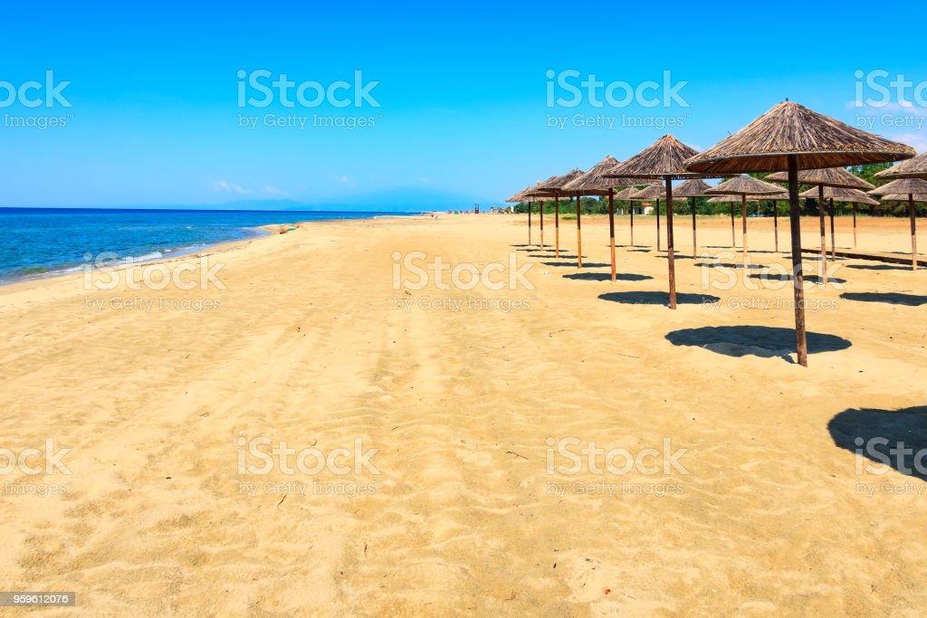 Fila de sombrillas de madera en la playa, mar - Foto de stock de Agua libre de derechos