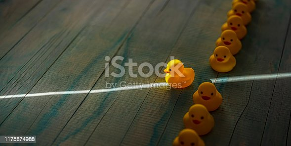 1068588904 istock photo Row of yellow rubber ducks in a formal line with one duck breaking free of the line heading towards a shaft of light shining through the darkness, scene set on an old blue and white weathered wooden panel background, conceptually representing water. 1175874988