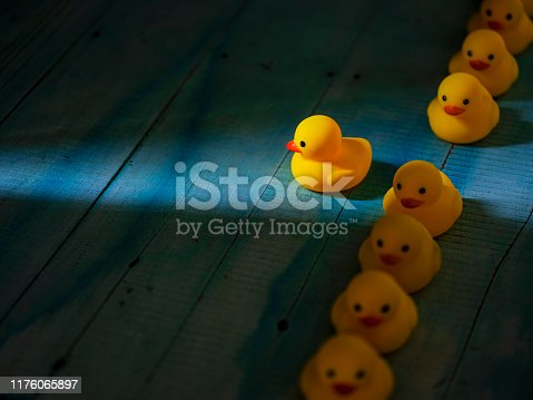 1068588904 istock photo Row of yellow rubber ducks in a formal line with one duck breaking free of the line heading towards a shaft of light shining through the darkness, scene set on an old blue and white weathered wooden panel background, conceptually representing water. 1176065897