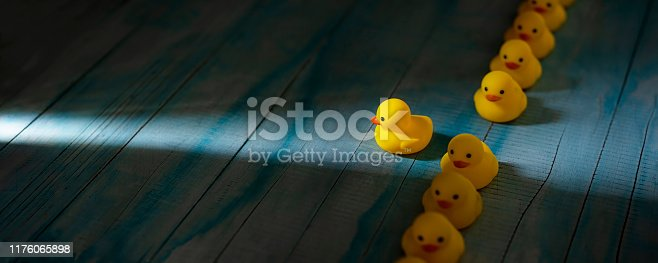 1068588904 istock photo Row of yellow rubber ducks in a formal line with one duck breaking free of the line heading towards a shaft of light shining through the darkness, scene set on an old blue and white weathered wooden panel background, conceptually representing water. 1176065898