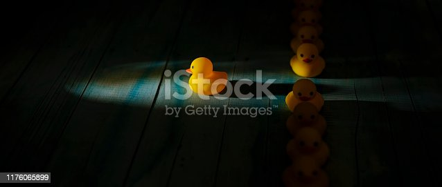 1068588904 istock photo Row of yellow rubber ducks in a formal line with one duck breaking free of the line heading towards a shaft of light shining through the darkness, scene set on an old blue and white weathered wooden panel background, conceptually representing water. 1176065899