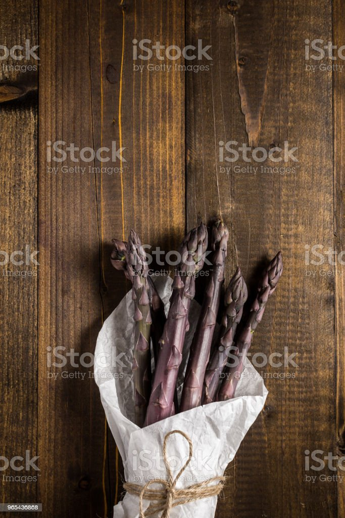 Row Purple Asparagus Close Up on Wooden Background royalty-free stock photo