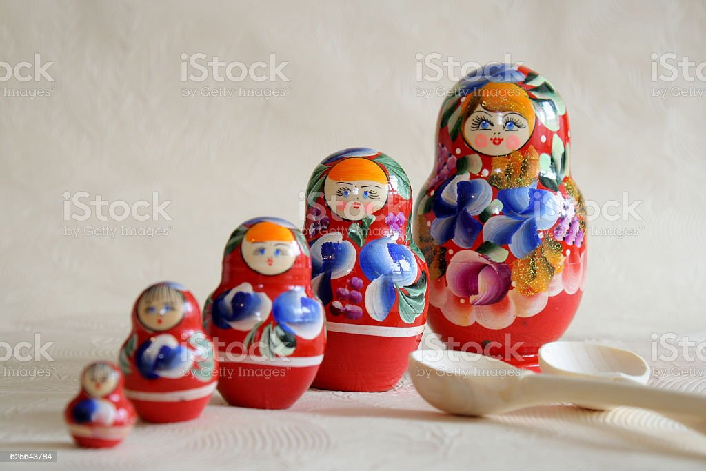 Row Russian Matryoshkas and two wooden spoons stock photo