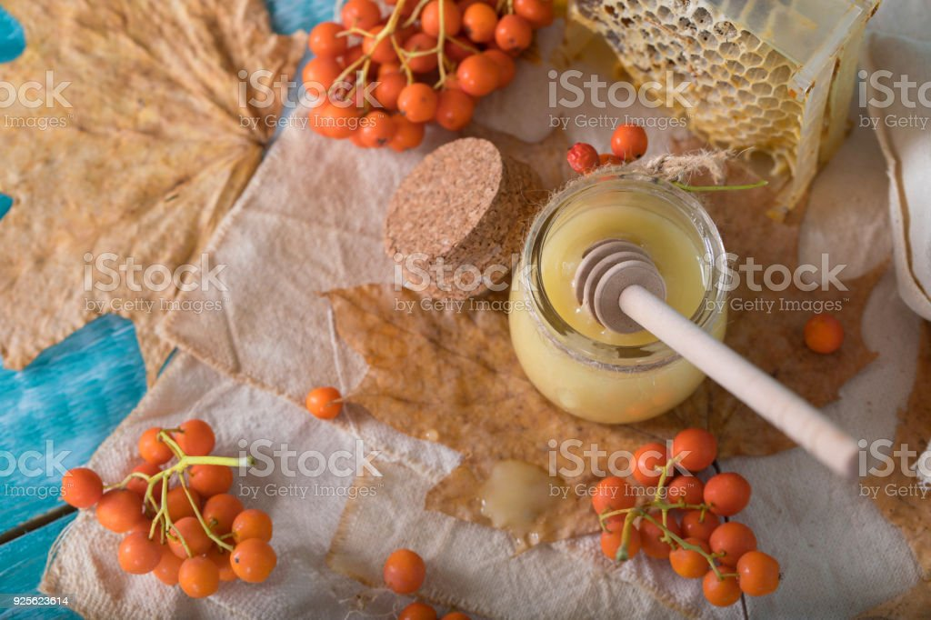 Rowan berries, honey and honeycomb on a sackcloth. stock photo