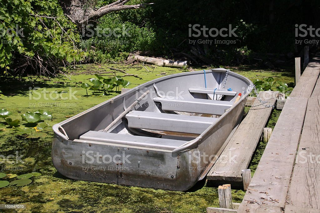 Rowboat in lake algae stock photo