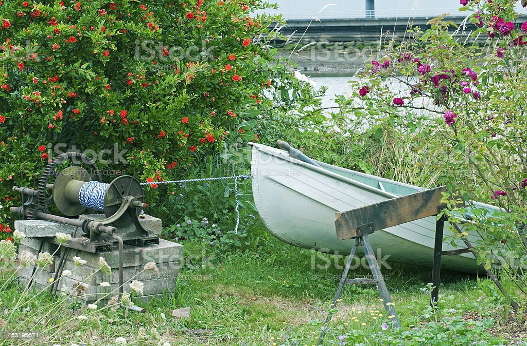 Rowboat tied to winch on riverbank royalty-free stock photo
