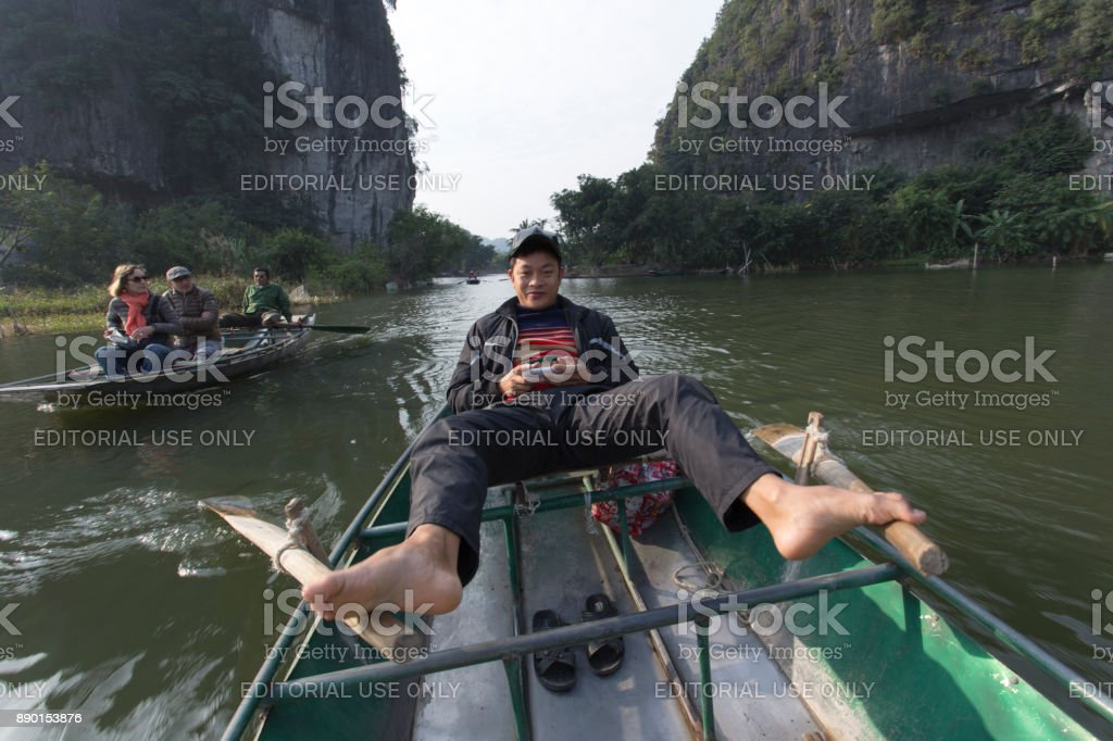 Rower using her feet to propel oars stock photo