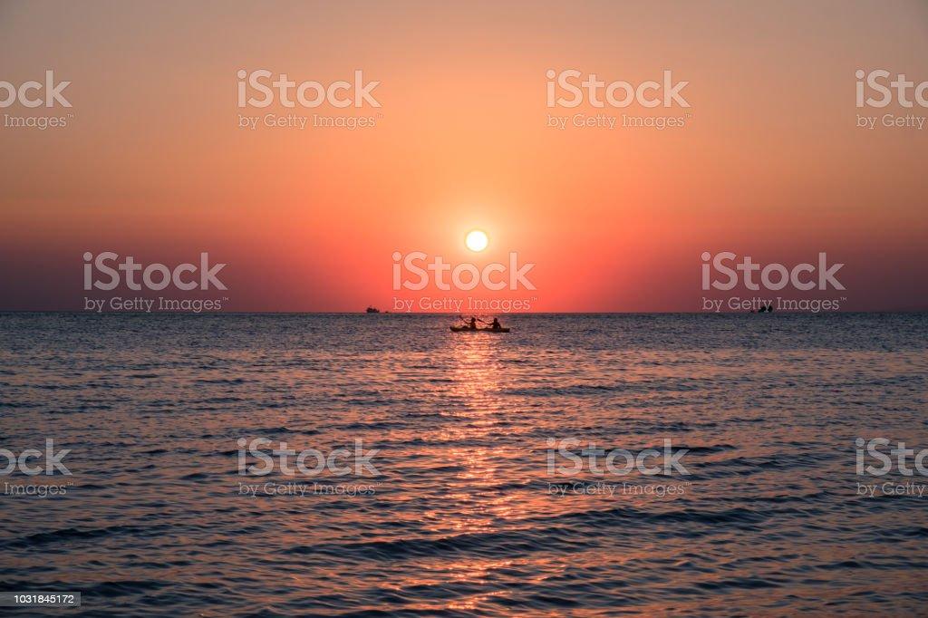 Rowing boat at he sea wit orange sun stock photo