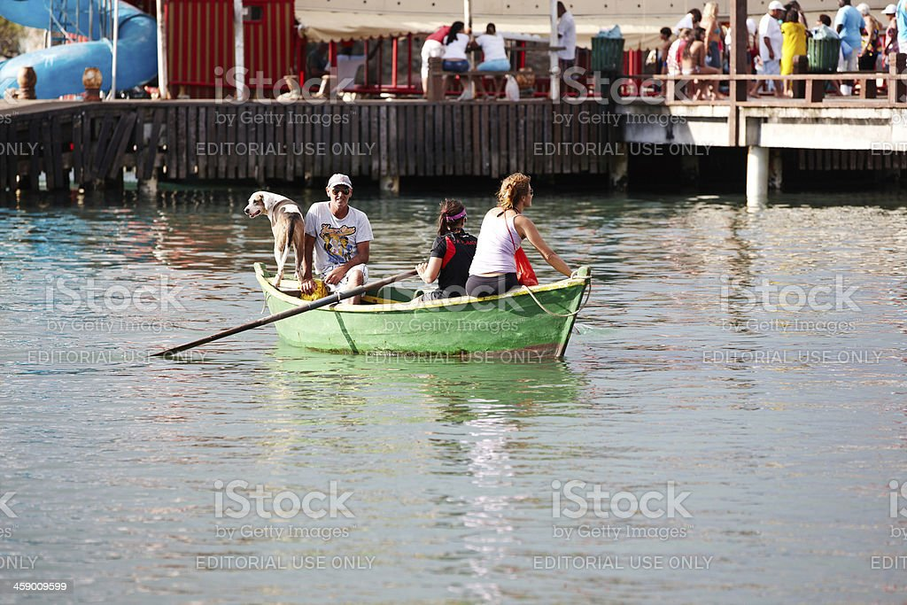 Rowing boat with people and dog onboard royalty-free stock photo