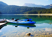 Rowing boats and canoes at a pier at the Black Lake, Montenegro