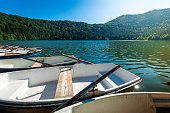 Wide angle color image depicting white rowboats moored up in a row on a glittering tranquil lake in the middle of summer.