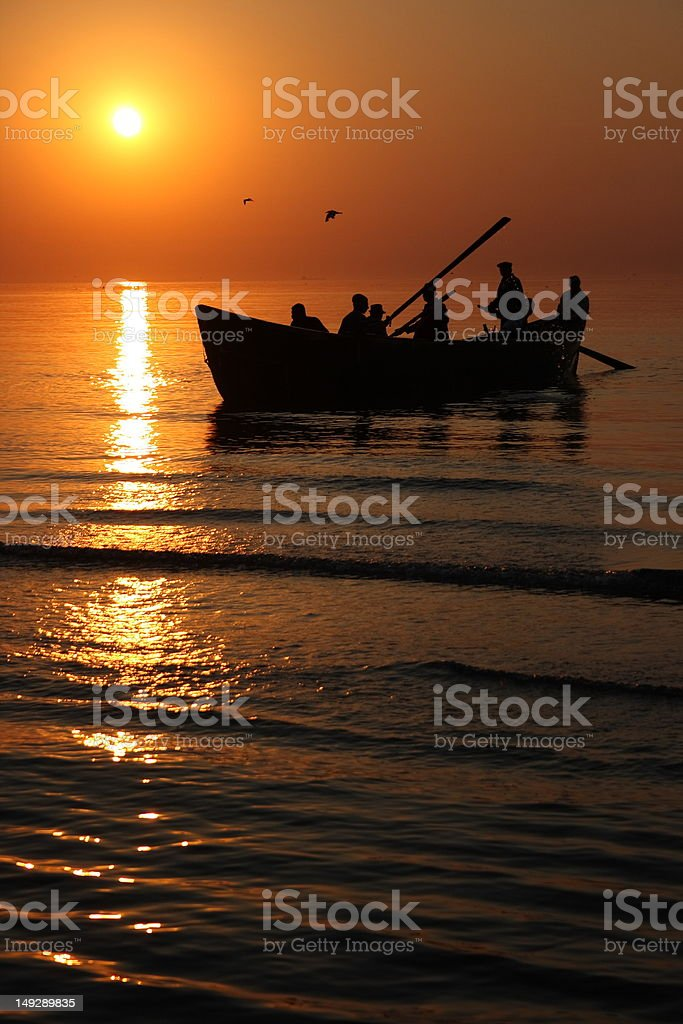 Rowing fishermen at sunrise royalty-free stock photo
