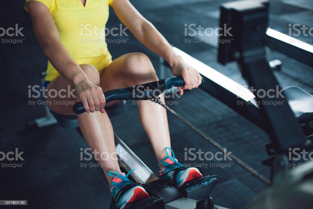 Remo en el gimnasio. Joven formación usando la máquina de remo - foto de stock