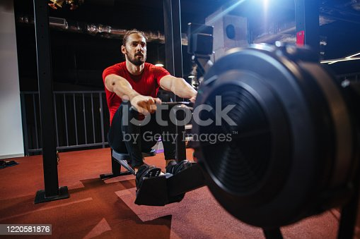 Young man doing rowing machine exercises at the gym