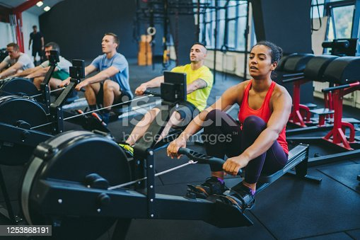 People in the gym exercising on rowing machines